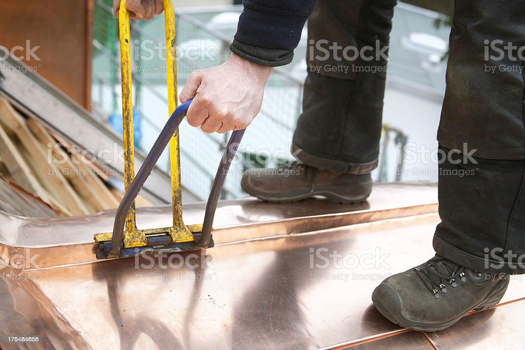 Working roofer with copper stock photo