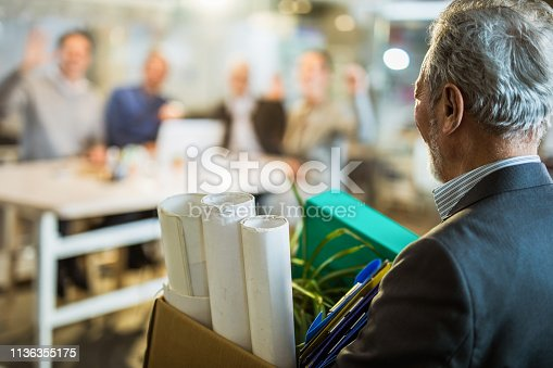 Retired senior businessman coming back to the office while carrying his belongings.