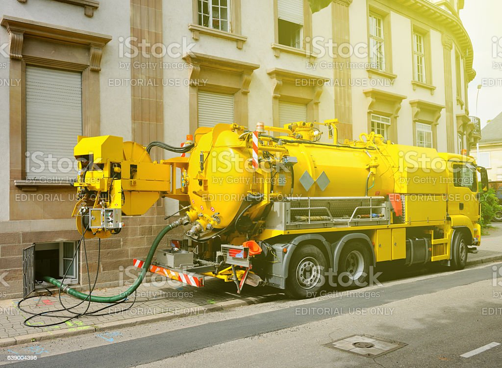 Working Sewage truck working in urban city environment stock photo