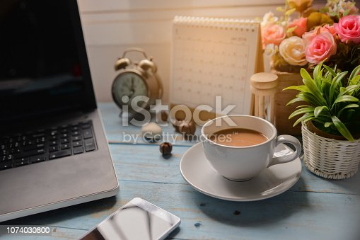 1073023470 istock photo Working space at home,Cup of Coffee with Desktop laptop,Calendar 2019,smartphone,clock and pot of rose flower on blue wooden desk.Urban Lifestyle concept 1074030800