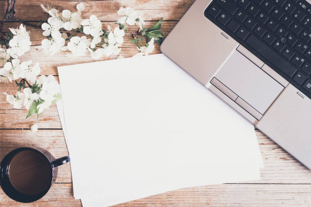 Working space with laptop spring flowers stock photo