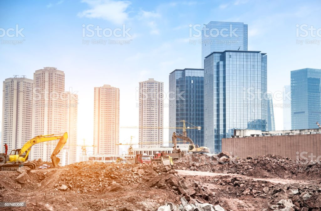 Working tall cranes inside place for with tall buildings under construction under a blue sky stock photo
