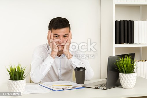932342408istockphoto Working tired Asian man in front of computer in office 1174803256