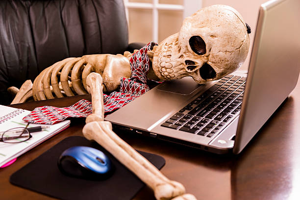 Working to death.  Business man's skeleton using laptop in office. stock photo