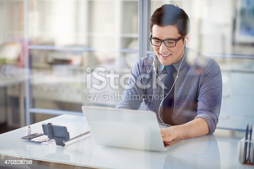 Young office worker typing on laptop and listening to music with earphones, monopod with smartphone near him