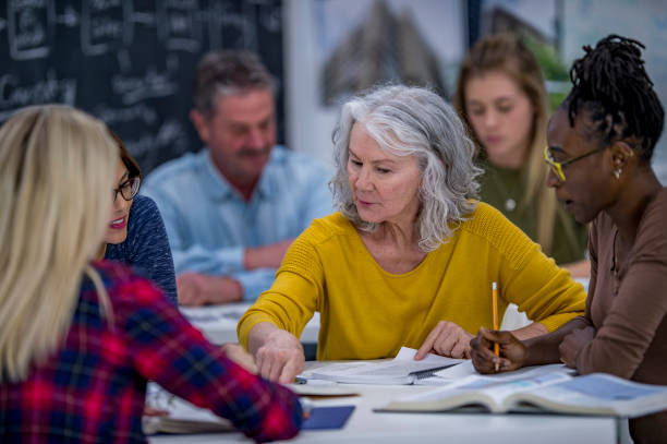 Working Together On A Project A group of university students are indoors in a study hall. They are having a group discussion. A Caucasian senior woman is reading out loud from a textbook. adult learning stock pictures, royalty-free photos & images