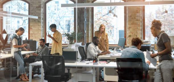 プロジェクトで一緒に作業します。クリエイティブオフィスで一緒に働く若い男女混合人種ビジネスマンのグループ。チームビルディングのコンセプト。オフィスライフ - オフィス ストックフォトと画像