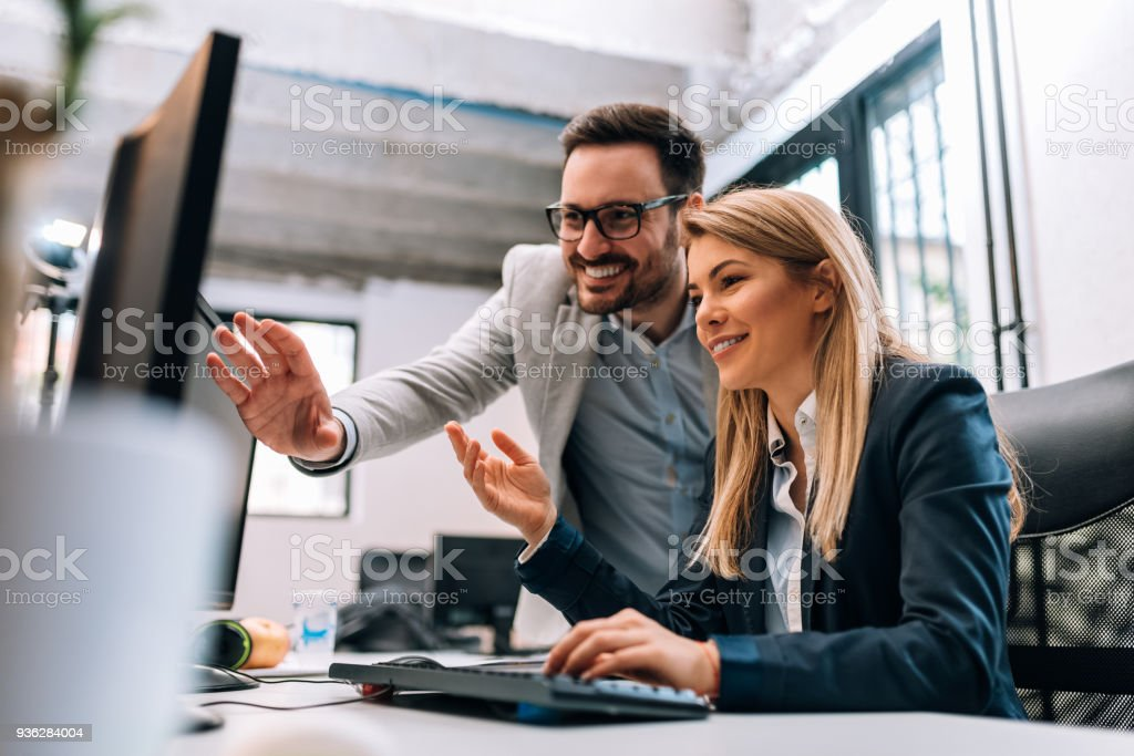 Working together on project. Two young business colleagues working on computer stock photo