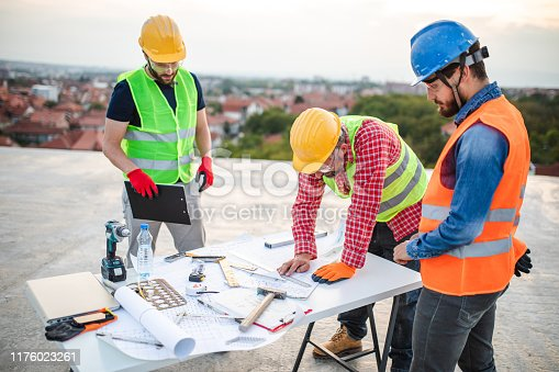 Team of architects revising blueprints and project implementation on construction site over table