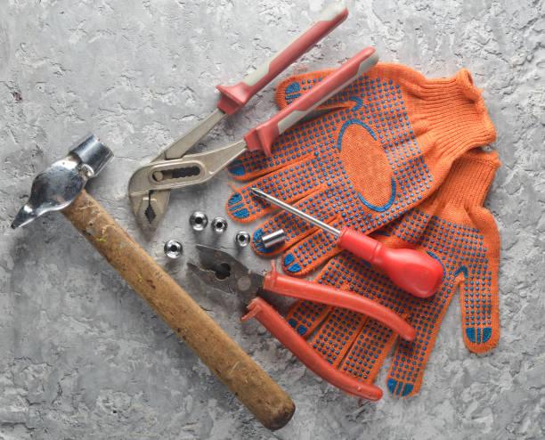 arbeitswerkzeug auf eine graue betonfläche. handschuhe, hammer, zangen, schraubendreher, zangen, schraubenzieher zu arbeiten. ansicht von oben. - diy ordner stock-fotos und bilder