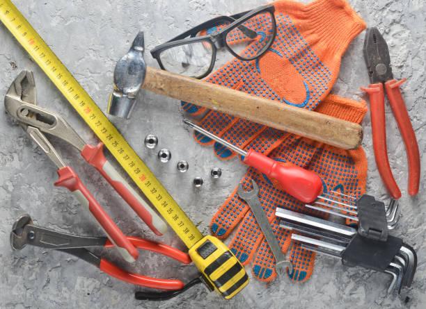 arbeitswerkzeug auf eine graue betonfläche. handschuhe, hammer, zangen, schraubendreher, zangen, schraubendreher, sechskant-schraubenschlüssel, skale zu arbeiten. ansicht von oben flach legen. - diy ordner stock-fotos und bilder