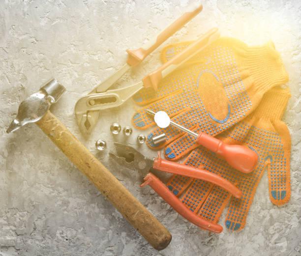 arbeitswerkzeug auf einer grauen betonoberfläche. arbeitshandschuhe, hammer, schnapper, schraubenzieher, zangen, schraubenzieher. top view. - diy ordner stock-fotos und bilder