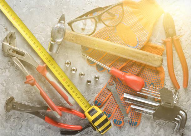arbeitswerkzeug auf einer grauen betonoberfläche. arbeitshandschuhe, hammer, schnapper, schraubenzieher, zangen, schraubenzieher, sechseckiger schraubenschlüssel, lineal. top aussicht, flach gelegen. - diy ordner stock-fotos und bilder