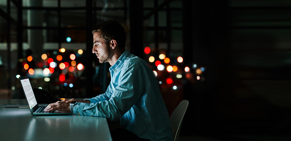 Shot of a businessman working on a laptop in an office at night