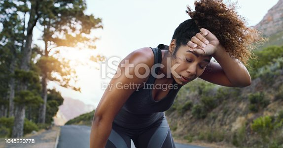 Shot of a sporty young woman taking a break while exercising outdoors