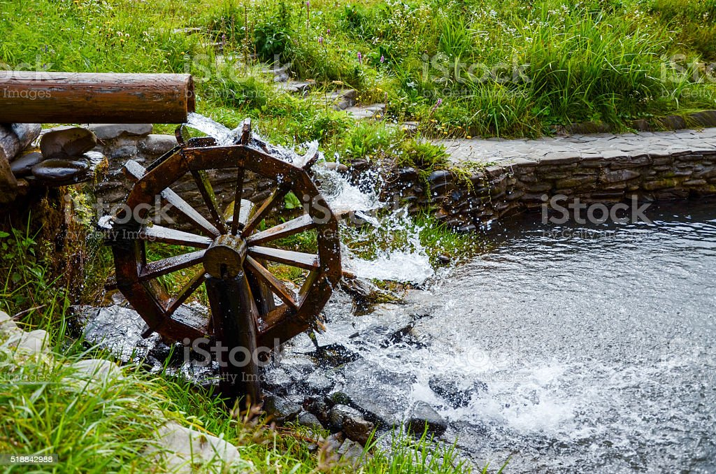 Working watermill wheel with falling waterin the village. stock photo