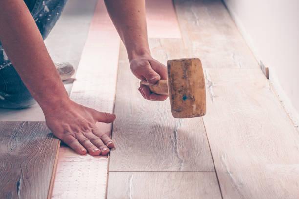 arbeiten mit einem hammer-clogs, die das laminate board einrastet, professionelle verlegung von bodenbelägen, laminat - wärmeplatte stock-fotos und bilder