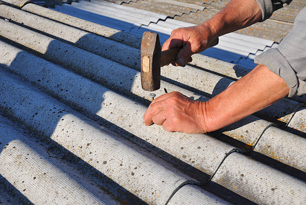 Working with asbestos roof shingles stock photo