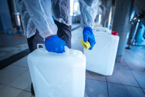 Working with chemicals. Unrecognizable person technologist in white protective suit handling acid or detergent in chemical industry. Industrial worker opening plastic canister to use chemicals. hazardous chemicals stock pictures, royalty-free photos & images