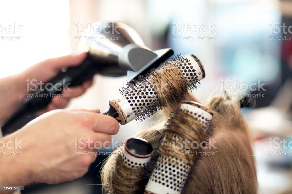 Working with comb and hair dryer at beauty salon royalty-free stock photo