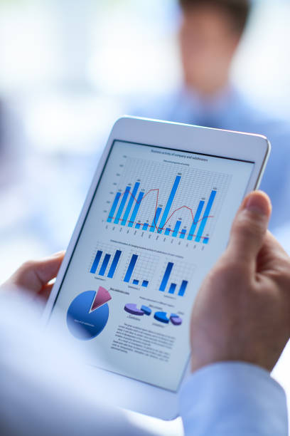 Working with data on tablet Modern businessman working on tablet to look through report financial report stock pictures, royalty-free photos & images
