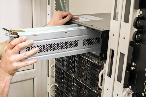 Working with equipment in the datacenter rack. Replacing the battery in an uninterruptible power supply. Changing the power module in the server room close-up.