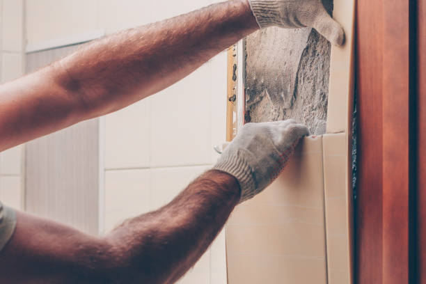 Working with his hands carefully removes old tiles from the wall stock photo