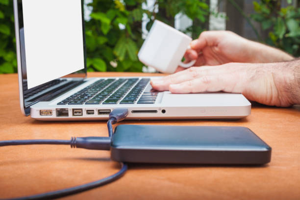 Working with laptop and cup of coffee Working with laptop and cup of coffee external hard disk drive stock pictures, royalty-free photos & images
