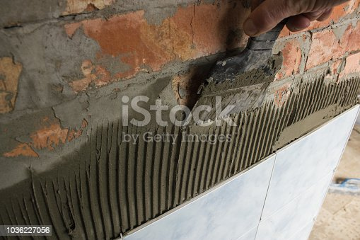 Man's hand tiling a bathroom red brick wall with mortar