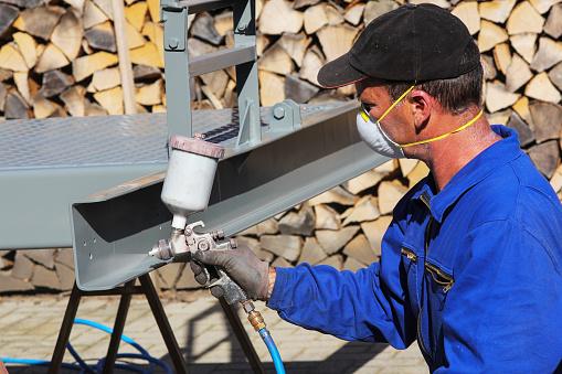 istock Working with paint spray gun 615396920