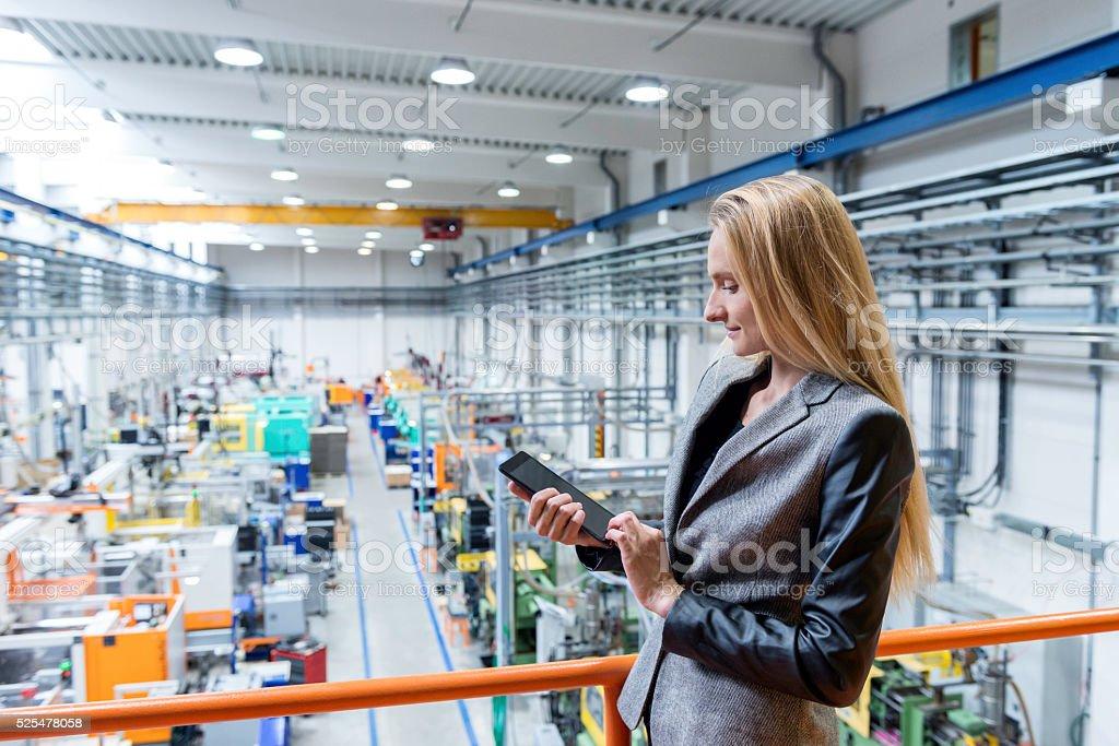 Trabalhando com tablet no futurista fábrica - foto de acervo
