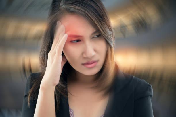 arbeiterin hat kopfschmerzen gegen grauen hintergrund, gutartiger paroxysmal positionsvertigo: bppv, konzept mit krankheit und gesundheit. - höhenangst stock-fotos und bilder