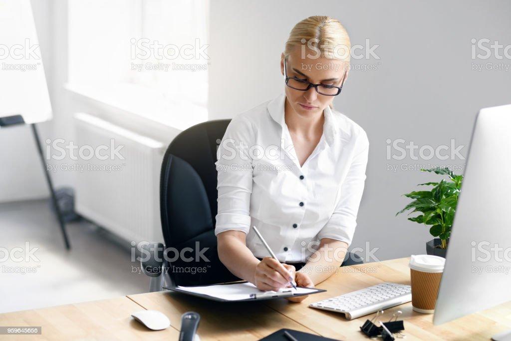 Trabajo mujer tomando notas en la oficina - Foto de stock de Accesorio para ojos libre de derechos