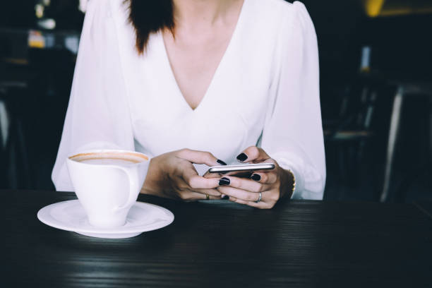 working woman using smart phone in cafe stock photo