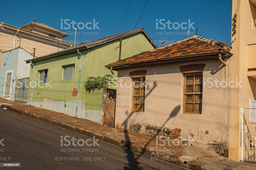 Working-class shabby colored houses in an empty street on a sunny day at San Manuel. stock photo