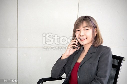 Workingwomen smiling and talking to mobile phone to welcome good news