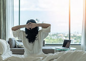istock Work-Life balance and life quality concept with woman rear view in rest relaxing on bed, take it easy in modern hotel guest room or luxury home living room with beautiful business city urban scene 1285704243