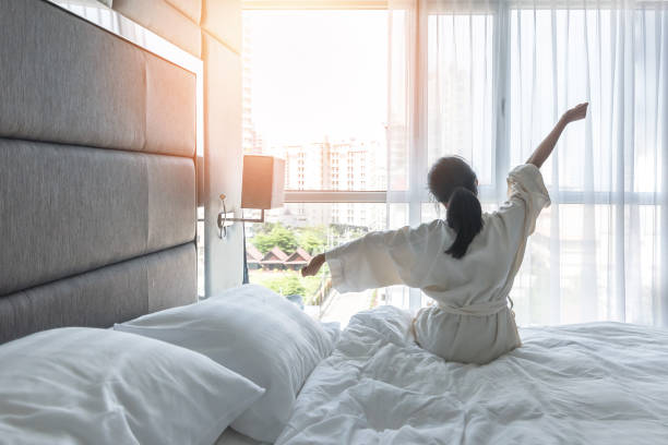 Work-life quality balance concept with lazy lifestyle of Asian girl on bed relaxing in comfort city hotel bedroom, take it easy, resting from good sleep waking up on weekend morning having a good day stock photo