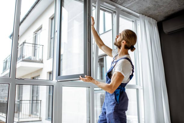Workman adjusting window frames at home Workman in overalls installing or adjusting plastic windows in the living room at home replacement stock pictures, royalty-free photos & images