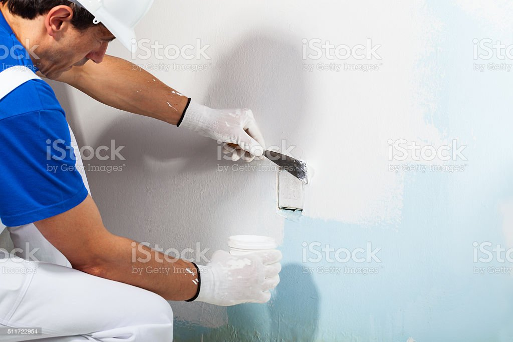 Workman Applying Plaster with Putty Knife stock photo