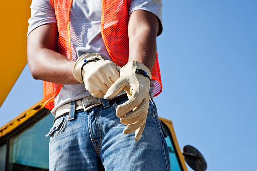 Low angle, cropped view of an African American young man putting on work gloves.  He is a construciton worker, wearing an orange safety vest and jeans.  Part of the crane is visible behind him, against the clear, blue sky.