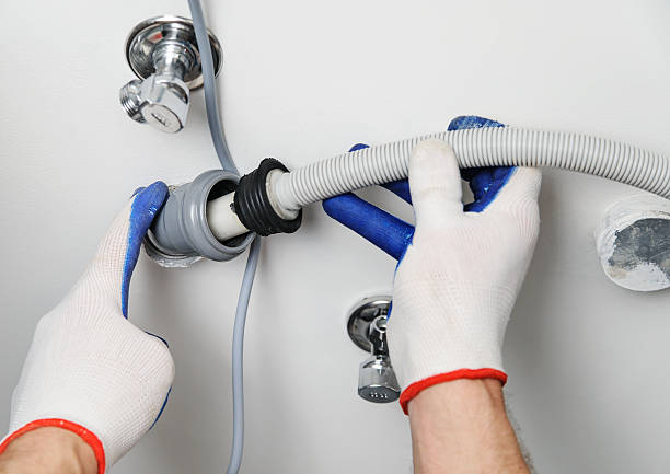 Workman attaches a drain hose to a sewage pipe. Installation of household appliances. Workman attaches a drain hose to a sewage pipe. hose stock pictures, royalty-free photos & images