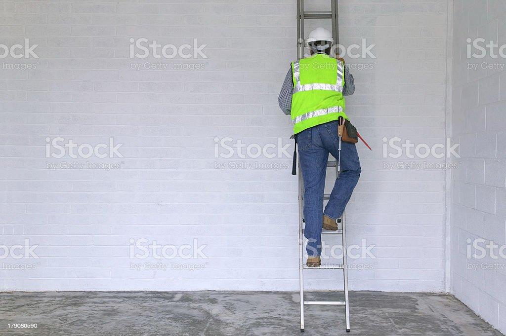 Workman climbing a ladder stock photo