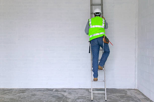 Workman climbing a ladder stock photo