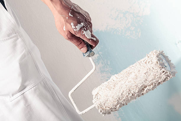 workman hand holding dirty paintroller - painter stock photos and pictures