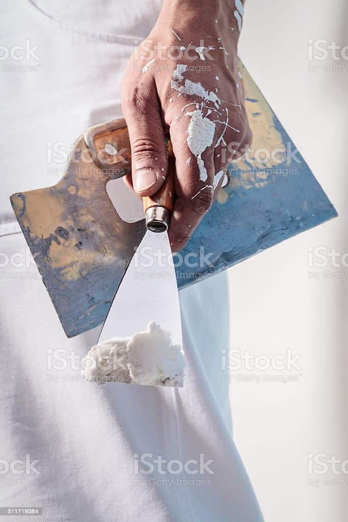 Workman Hand holding Putty Knife with Plaster stock photo