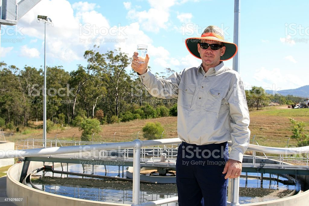 Workman Holding Clean Recycled Water at a water treatment plant royalty-free stock photo