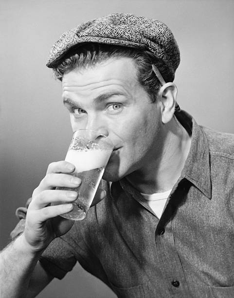 Workman in cap drinking beer in studio, (B&W), (Close-up), (Portrait) stock photo