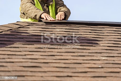 Building under construction concept. Workman installing roof asphalt shingles or tiles installed on top of the new residential house