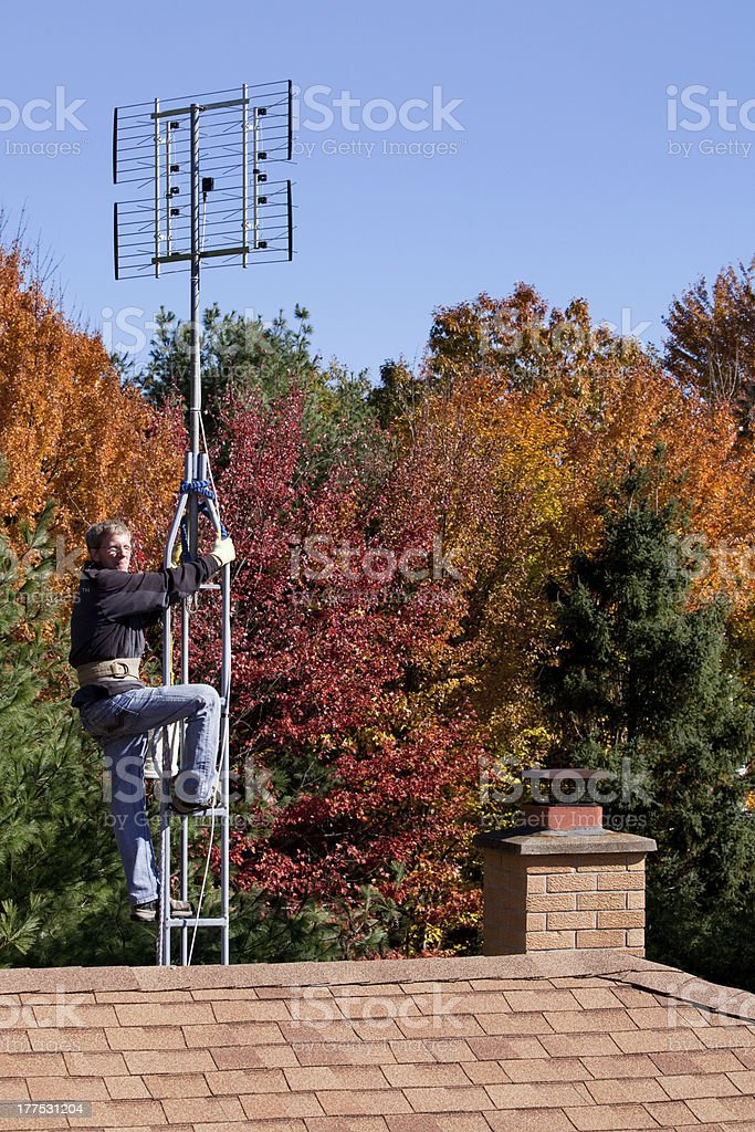 Workman installing HDTV digital antenna on a house stock photo